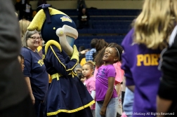 A young University of Toledo fan laughs with Rocksy Rockette, one of Toledo's mascots, before the game against Kent State University on Jan. 12, 2019. Rocksy is one of two astronaut mascots for the Toledo Rockets.
