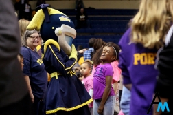 A young University of Toledo fan laughs with Rocksy Rockette, one of Toledo's mascots, before the game against Kent State University on Jan. 12, 2019. Rocksy and Rocky are the two astronaut mascots for the University of Toledo Rockets.