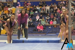 Kent State University gymnasts watch, cheer on and hold pads in place while one of their teammates performs on the uneven bars against Western Michigan University on March 1, 2019.