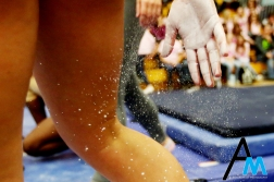 A Kent State University gymnast wipes chalk off of her hand before her performance on the beam against Western Michigan University on March 1, 2019.