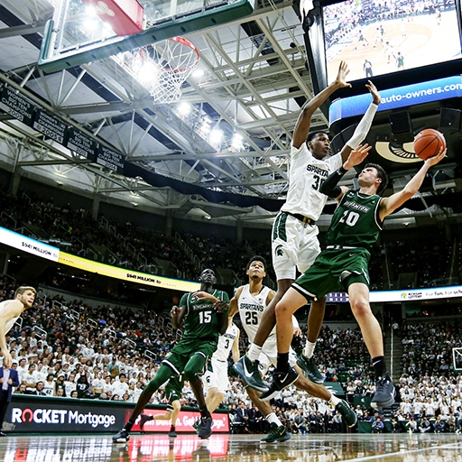 A Binghamton University Men's Basketball player takes a shot over Marcus Bingham Junior in the Breslin Center in Michigan