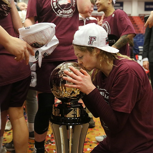 Mary Goulding of Fordham's Women's basketball team kisses the Atlantic 10 championship trophy in Pittsburgh, Pennsylvania