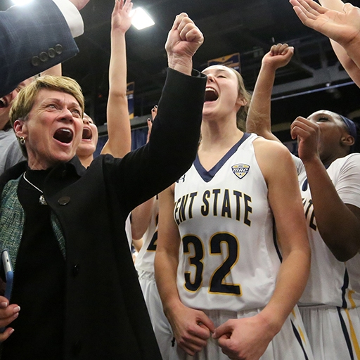 Former Kent State University President Beverly Warren celebrates with the Women's Basketball team after winning a game