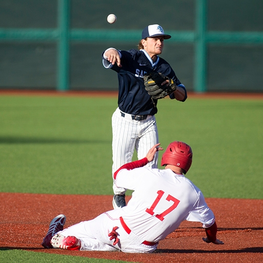 A University of San Diego baseball player throws over an Indiana University player at Bart Kaufman Field in Bloomington, Indiana